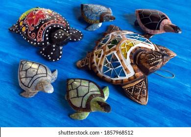 Groep kleurrijke houten zeeschildpadden op waterverf blauwe achtergrond.