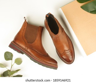 Women's brown shoes with perforations. Chelsea boots, magazine and leaves.