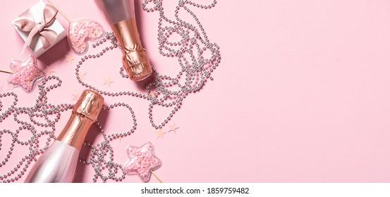新年とクリスマスのお祝いバナー、ロゼワインまたはシャンパン、ピンクの背景に美しい輝く装飾、デザイン用のコピースペース。グリーティングカードのモックアップの招待状。