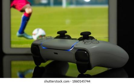 Controlador de juego Next Gen con juego de fútbol en la pantalla