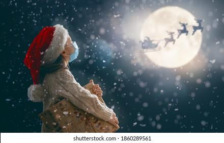 メリークリスマス!クリスマスプレゼントのかわいい小さな子供。月の空を背景にそりで飛んでいるサンタクロース。幸せな子供は休日を楽しんでいます。暗い背景に贈り物とフェイスマスクの女の子の肖像画。