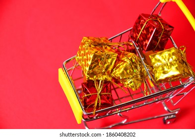 A boxes with a ribbon in a shopping trolley. Concept - buying a gift. on red background concept of online shopping for christmas or new year