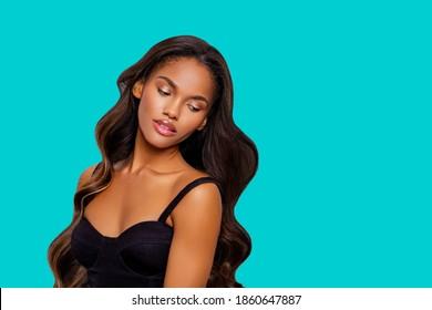 若いアフリカ系アメリカ人女性の美しさのスタイルの肖像画。化粧。ターコイズブルーの背景のスタジオでポーズをとる巻き毛のファッション黒人少女。隔離された。スタジオショット。