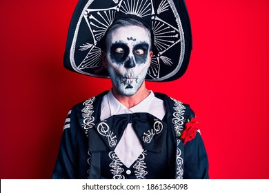Young man wearing mexican day of the dead costume over red making fish face with lips, crazy and comical gesture. funny expression.