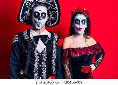 Young couple wearing mexican day of the dead costume over red making fish face with lips, crazy and comical gesture. funny expression.