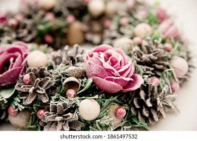 Festlicher Hintergrund mit Adventskranz. Weihnachtsstimmung. Handgemachte Dekoration mit Blumen und Frost. Natürliche rosa - lila Farbe.