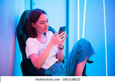 Young lady sitting on gaming chair with cellphone in hands. Playing online mobile game or browsing social networks resting in a room lit with neon color.