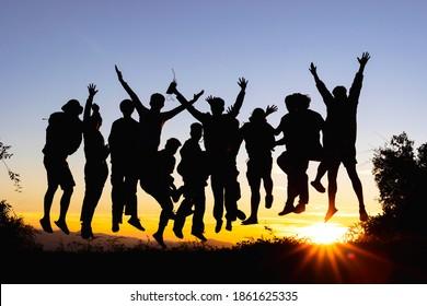 山に沈む夕日にジャンプする多くの人々のシルエットをグループ化、新年あけましておめでとうございますコンセプト、