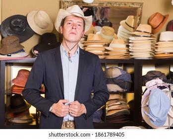 glücklicher erwachsener Mann probiert westlichen Hut am Einkaufszentrum an
