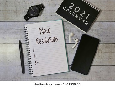 New resolutions text on white notepad surrounded by smartphone, men's watch, black pen and 2021 calendar.Flat lay concept.White wooden table background. Black and white theme