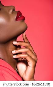 赤で隔離の顔に触れるアフリカ系アメリカ人の若い女性のトリミングされたビュー