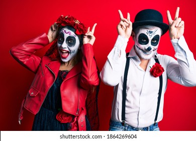 Couple wearing day of the dead costume over red posing funny and crazy with fingers on head as bunny ears, smiling cheerful