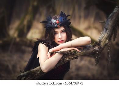 Linda chica joven en vestido oscuro criatura elfo de hadas en el retrato de bosque