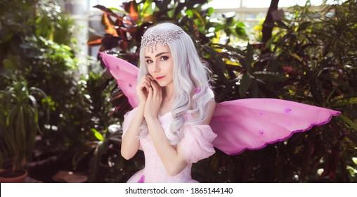 Atractiva chica joven vestida de hada en jardín verde con alas rosas