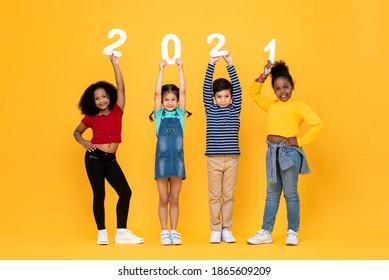 Nette gemischte Rassenkinder, die lächeln und 2021 Zahlen lokalisieren auf gelbem Hintergrund für Neujahrskonzepte halten