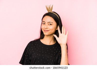 Junge chinesische Prinzessinfrau lokalisiert auf einem rosa Hintergrund, der eine Handy-Anrufgeste mit den Fingern zeigt.