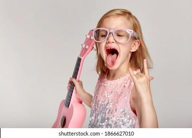 Rock'n'Roll-Musikkonzept. Nettes kaukasisches kleines Mädchen zeigt ihre Zunge in einem hellen rosa Kleid und Brille spielen die Ukulele auf einem grauen Studiohintergrund mit Kopienraum
