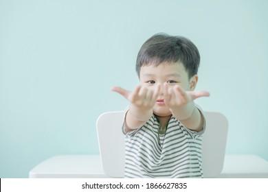 Foto des entzückenden kleinen glücklichen Jungen schießt ein Netz aus seiner Hand wie eine Spinne zu Hause. Speicherplatz kopieren.