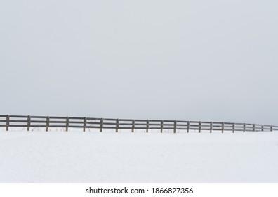 Der Winter schafft eine kalte Landschaft, die von einem endlosen Zaun in zwei Teile geteilt wird.