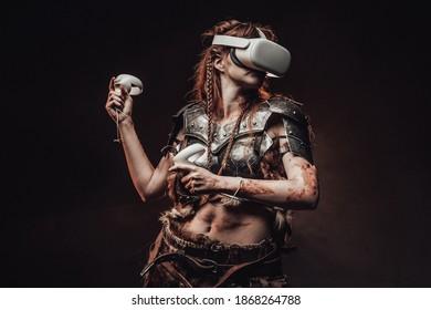 Portret van een barbaarse vrouw uit Noord gekleed in middeleeuws pantser poseren in donkere achtergrond met virtual reality headset.