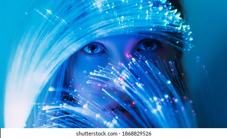 Fantasy portrait. Inner world. Fairytale mystery. Magic miracle. Curious female face with expressive eyes looking through optical fiber blue pink fluorescent neon light.