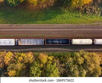 田舎の複線鉄道である貨物列車の航空写真。緑の草と黄色の葉を持つ秋の木々のある鉄道、上面図。交通インフラ、線路、秋の自然