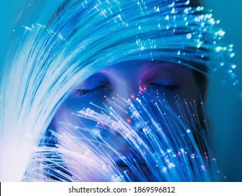Fantasy-Porträt. Magischer Traum. Phantasie unbewusst. Gedankenharmonie. Friedliches Frauengesicht mit geschlossenen Augen hinter dem blauen rosa fluoreszierenden Neonlicht der optischen Faser.