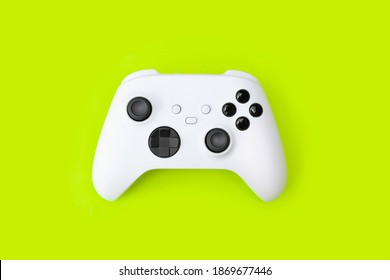 White next gen game controller on green background.