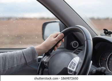 Mano masculina en el volante de un automóvil Mitsubishi. Lluvia de otoño fuera de la ventana. Conducción cómoda de SUV.