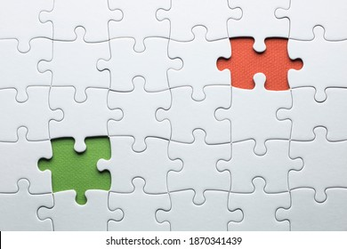 A puzzle is missing two pieces to be completed in different colors. white pieces and one piece in green and one in orange to add text