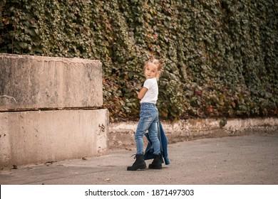 Stilvolles kleines Mädchen in Jeans und einem weißen T-Shirt geht die Straße entlang. Mädchen 7 Jahre altes kleines Modell, schönes Kind