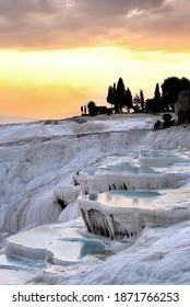 Pamukkale al atardecer. Pamukkale es un paraje natural en Denizli, en el suroeste de Turquía. La zona es famosa por un mineral de carbonato dejado por el flujo de agua termal.