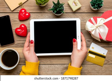 Girl holds tablet, chooses gifts, makes purchase, cup of coffee, debit card, two hearts on wooden table Top view Flat lay Holiday shopping list, Happy Valentine's day, online shop concept Mock up