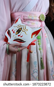 Woman wearing kimono or hanfu and a fox mask. Traditional japanese fox masks called kitsune. Chinese, Japanese traditional concept.