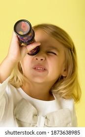 小さな女の子が望遠鏡や万華鏡をのぞき込みます。