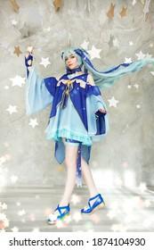 Linda chica joven vestida como mago con varita mágica de pie alrededor de retrato de estrellas
