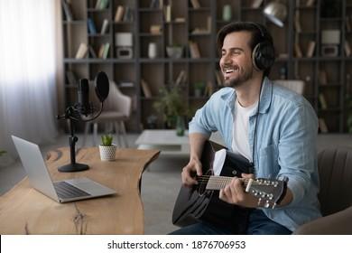幸せなミレニアル世代の男性アーティストの広いバナービューは、コンピューターでギターを取るオンラインビデオウェブカメラのレッスンを保持します。笑顔の若い男の歌手や作曲家は、自宅のラップトップで楽器時計の音楽チュートリアルを使用しています。