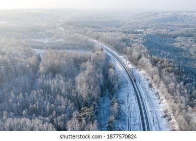 リトアニア、ビリニュスの雪に覆われた森を走る列車の空中白い冬のショット
