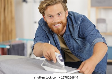 portrait of smiling young man ironing cloth
