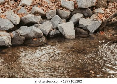 Eine Nahaufnahme eines Flusswasserstroms, umgeben von Felsen