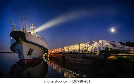 Ship with searchlight at night. The boat is at the pier. Moonlit night, dark water. Reflection in the river. Panoramic image.