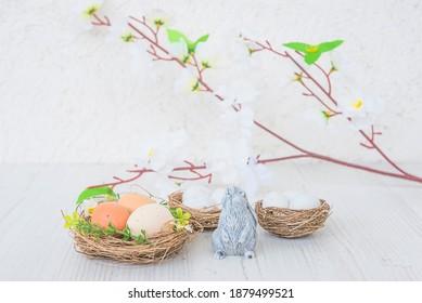 Osterferiengrußkarte. Drei Nester mit Eiern, Kaninchen und Zweig mit weißen Blüten