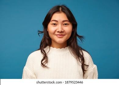 Innenfoto der angenehm aussehenden jungen dunkelhaarigen asiatischen Frau mit der gewellten Frisur, die positiv an der Kamera lächelt, während sie gegen blauen Hintergrund steht