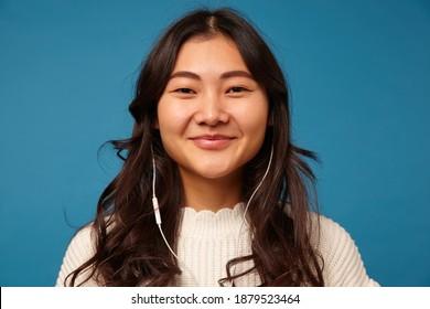 Porträt einer fröhlichen attraktiven jungen dunkelhaarigen Frau mit Kopfhörern, die fröhlich in die Kamera lächeln, während sie über blauem Hintergrund in weißen Strickkleidern stehen