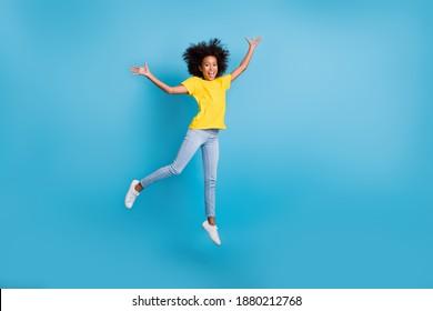 小さなかわいいアフロアメリカンガールジャンプエアレイズ手を着用ジーンズ黄色のTシャツの完全な長さの写真は青い色の背景に分離されました