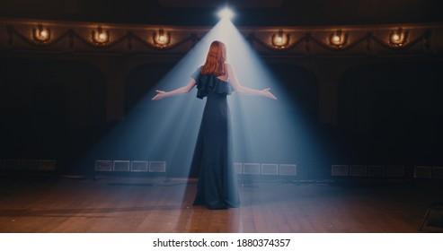エレガントなドレスを着た若い女性がジェスチャーをし、観客と情熱的に話し、劇場でのパフォーマンスの終わりに立ち去ります