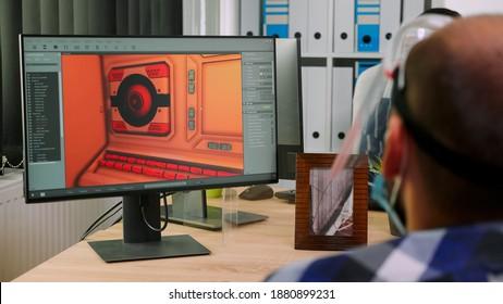 covid-19パンデミックの間に新しい通常のスタジオオフィスからのプロジェクトで働いている保護フェイスマスクで車椅子に座っている固定化されたゲーム開発者。社会的距離を尊重する障害者。