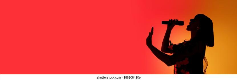 チラシ。ネオンの光の中でオレンジ色のグラデーションスタジオの背景に分離された若い女性歌手のシルエット。実行中の美しい影。人間の感情、表現、広告、音楽、アートの概念。
