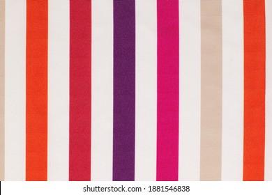 赤、オレンジ、ピンク、紫のストライプのクローズアップ綿生地のテクスチャ。コピースペースと抽象的な背景。