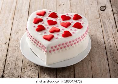 Herzkuchen für Valentinstag, Muttertag oder Geburtstag, verziert mit Herzzucker auf Holztisch